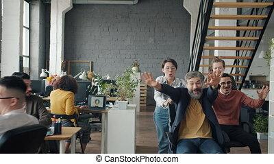 Slow motion of crazy businesspeople enjoying office chair race having fun during work break