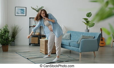 Slow motion of crazy pregnant woman dancing and singing in remote control in modern house. Modern youth lifestyle and pregnancy concept.