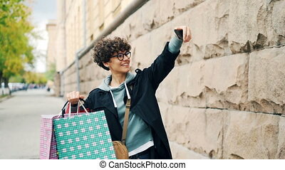 Slow motion of curly-haired woman taking selfie with colorful shopping bags standing outdoors, holding smartphone and smiling. City and modern technology concept.
