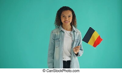 Slow motion of cute African American girl holding German flag and smiling