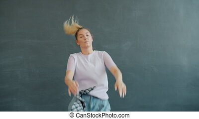 Slow motion of cute young blonde dancing on grey background twerking indoors enjoying hip-hop music. Youth culture and active lifestyle concept.