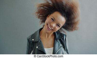 Slow motion of cute model Afro-American girl having fun waving head in studio
