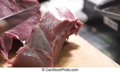 Slow motion of cutting big piece raw fresh of meat on cutting board