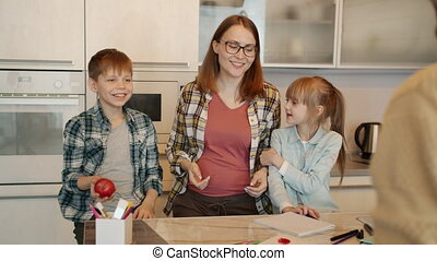 Slow motion of dad playing with son throwing apple while woman and girl doing homework in kitchen at home