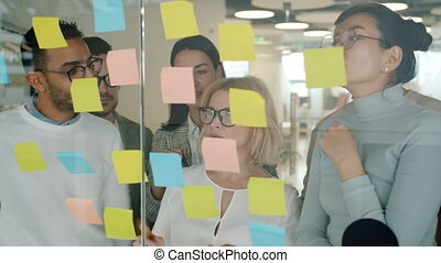 Slow motion of diverse group of people colleagues working with sticky notes on glass board