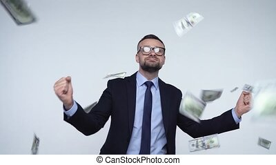 Slow motion of dollars falling on formally dressed man -...