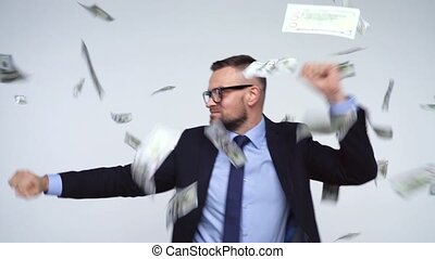 Slow motion of dollars falling on formally dressed man