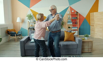 Slow motion of elderly couple dancing at home enjoying romantic music together