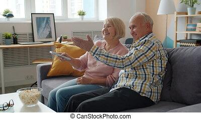 Slow motion of elderly man and woman watching TV laughing talking enjoying movie