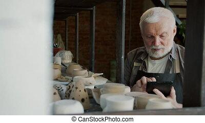Slow motion of elderly man potter using tablet during ...