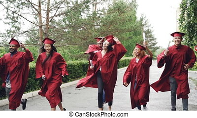 Slow motion of emotional graduates happy girls and guys running with diplomas and laughing, pretty girl is taking off mortar-board and waving it. Small rain is visible