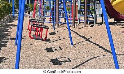 Children swings at empty playground during coronavirus AKA covid-19 virus threat captured in slow motion