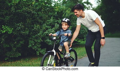 Slow motion of excited boy riding bicycle and laughing while...
