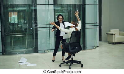 Slow motion of excited businesswomen whirling in rolling...