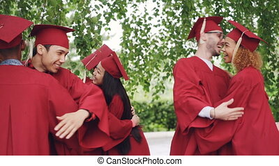 Slow motion of excited young people graduating students in gowns and hats are hugging congratulating each other on graduation, laughing and celebrating end of education.