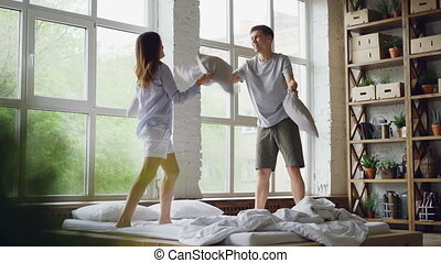Slow motion of excited young people having pillow fight on...