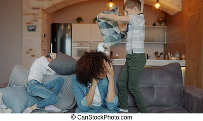 Slow motion of exhausted nanny mixed race lady suffering from migraine holding head while noisy kids boy and girl are fighting pillows on couch