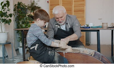 Slow motion of experienced potter in dirty apron teaching little boy to work with pottery wheel shaping clay making earthenware. Crafts and workshop concept.