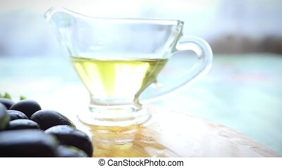 Slow motion of Extra virgin healthy Olive oil in bowl with fresh olives on the table