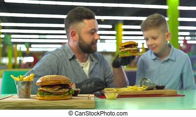 Slow motion of father and son eating burger at restaurant. -...