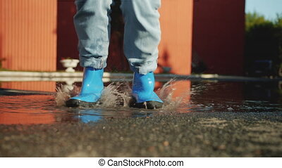 Slow motion of feet in bright blue gumboots jumping in pool having fun on autumn day enjoying outdoor activity. Lifestyle, entertainment and footwear concept.