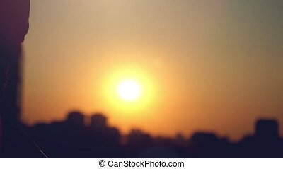 Slow motion of female and male hands showing a thumb up gesture at city sunset through the sun