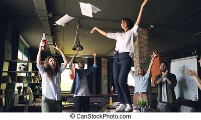 Slow motion of female manager dancing on desk at corporate party and throwing pile of documents in air while team members are laughing and clapping hands.