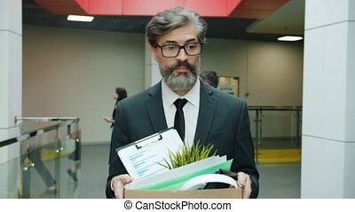 Slow motion of depressed fired businessman walking in hall with box of belonging after dismissal feeling unhappy and hopeless. People and work concept.