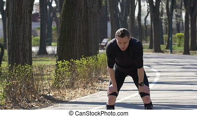 Slow motion of fit male jogger after a quick break catching...
