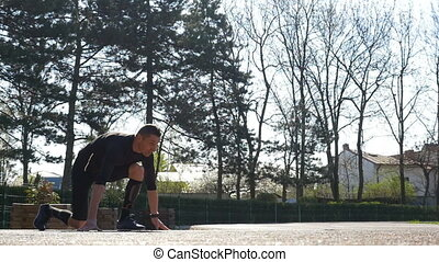 Slow motion of fit runner starting running from block start position on a track