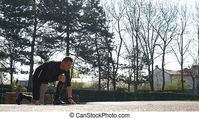 Slow motion of fit runner starting running from block start...