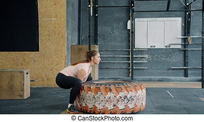 Slow motion of fit young sportswoman lifting heavy rubber tyre working out in gym during crossfit training. Active people, workout and bodycare concept.