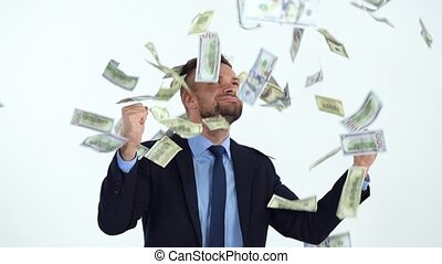Happy formally dressed man is delighted with the fact that a lot of dollar bills are fall on him. Slow motion