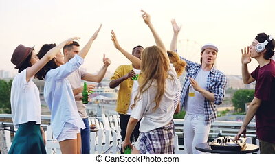 Slow motion of happy friends dancing with raised hands enjoying music rhythm and laughing while deejay is working with mixing console. Rooftop party, modern lifestyle and youth concept.