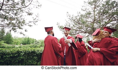 Slow motion of friends graduating students doing high five and embracing each other wearing mortarboard caps and gowns and holding diplomae. Campus, events and people concept.