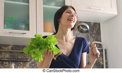 Slow motion of funny woman cook dance and sing with big ladle and lettuce while cooking in kitchen