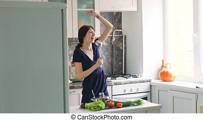 Slow motion of funny woman cook dance and sing with big ladle while cooking in kitchen at home