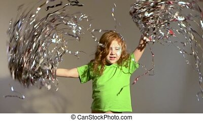 Slow motion of ginger girl waving tinsel in her hands. -...