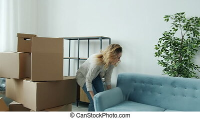 Slow motion of girl and guy moving furniture carrying new sofa to house during relocation then sitting and enjoying rest. Housing and family concept.