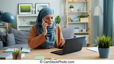 Slow motion of girl in hijab using laptop then talking on...