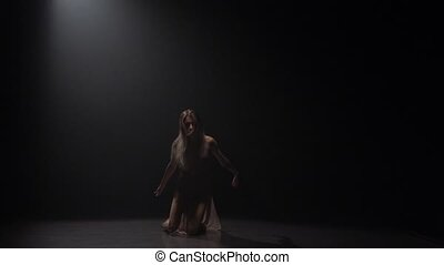 Slow motion of gorgeous maiden dancing contemp in dark...