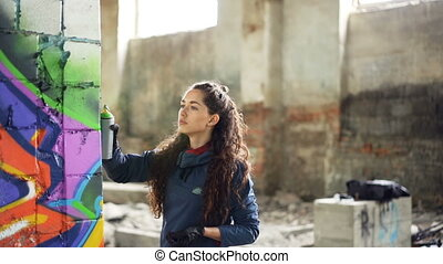 Slow motion of graffiti artist painting on wall in abandoned...