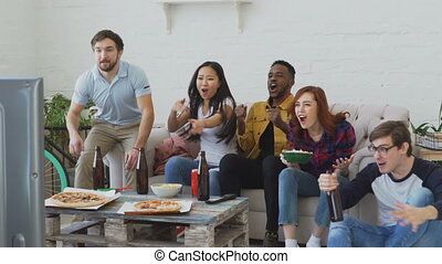Slow motion of group of happy friends watching sports game on TV at home indoors. They are yelling while their favorite team win competition