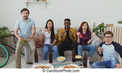 Slow motion of group of happy friends watching sports game...