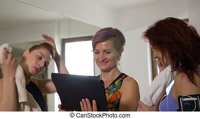Slow motion of group of smiling women after training talking in fitness gym using digital tablet pc