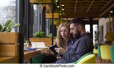 Slow motion of guy and a girl discuss their startup with a tablet sitting in a cafe