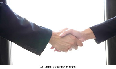 Slow motion of hand shaking between a man and woman in suit