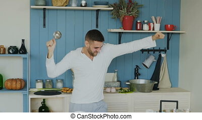 Slow motion of handsome young funny man dancing and singing with ladle while cooking in the kitchen at home