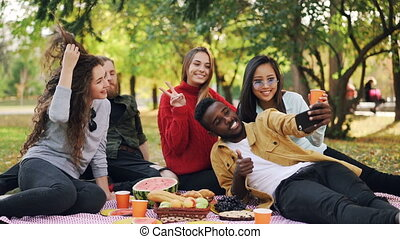 Slow motion of happy African American man taking selfie with friends on picnic using smartphone, people are posing with drinks and showing hand gestures.
