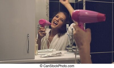 Slow motion of happy beautiful young woman in a bathrobe singing and dancing in front of the bathroom mirror
